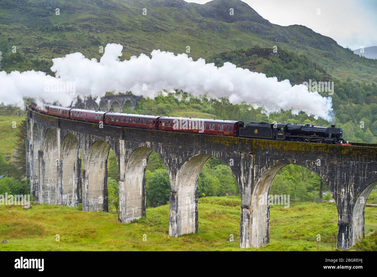 'The Jacobite' locomotive steam train on West Highland Rail crosses famous Glenfinnan Viaduct tourist spot in the Highlands of Scotland Stock Photo