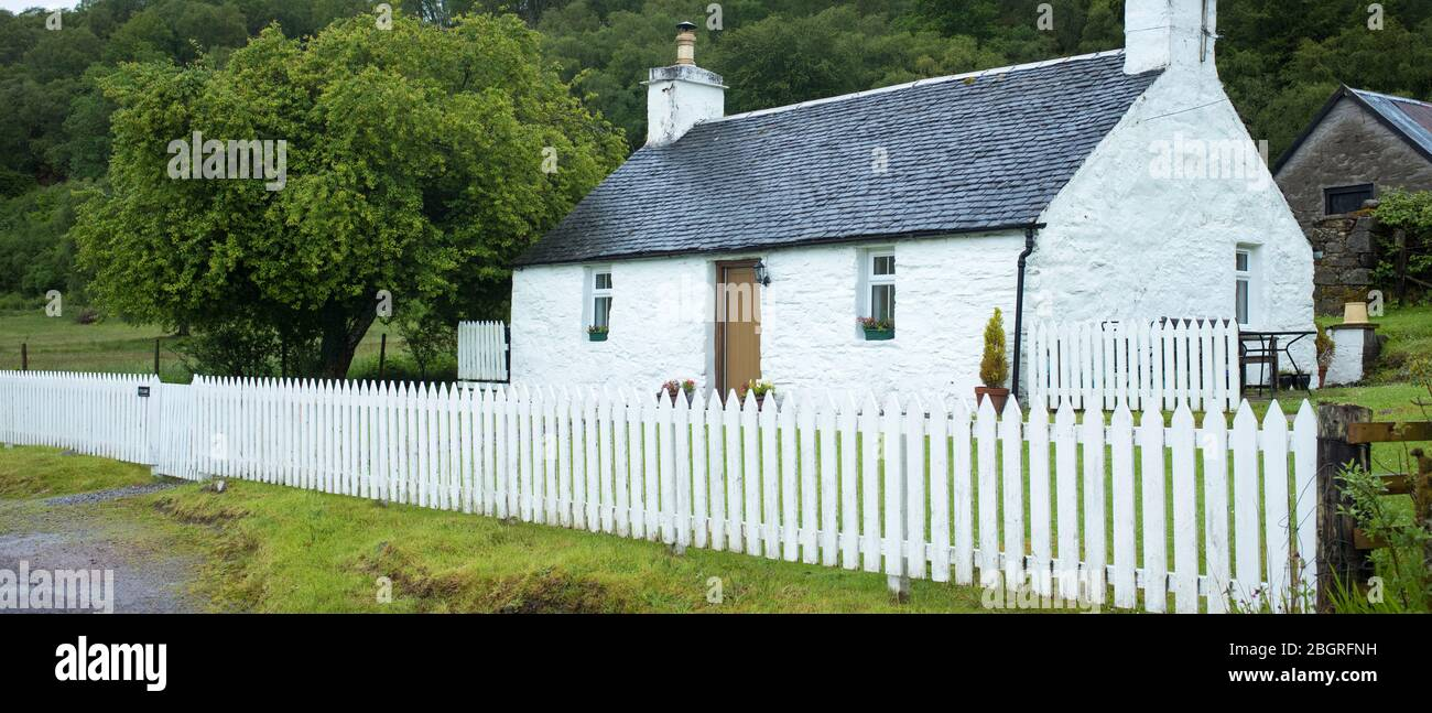 Quaint traditional whitewashed cottage with white paling fence and tiled roof in Appin, Argyll and Bute, Scotland Stock Photo