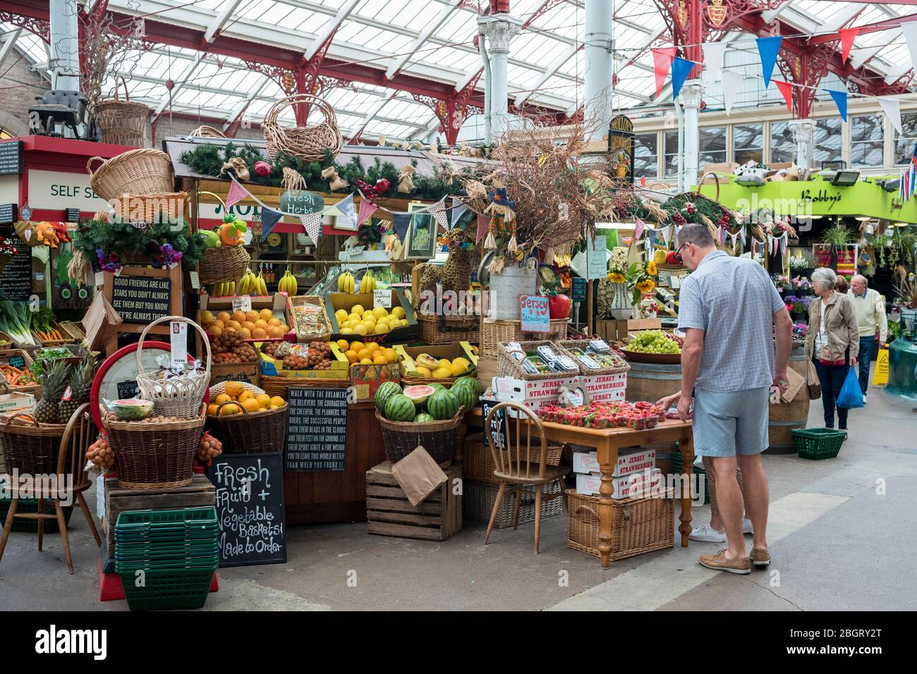 Fruit and other items on sale at St Helier Central Market in historic Victorian market hall, in Jersey, Channel Isles Stock Photo