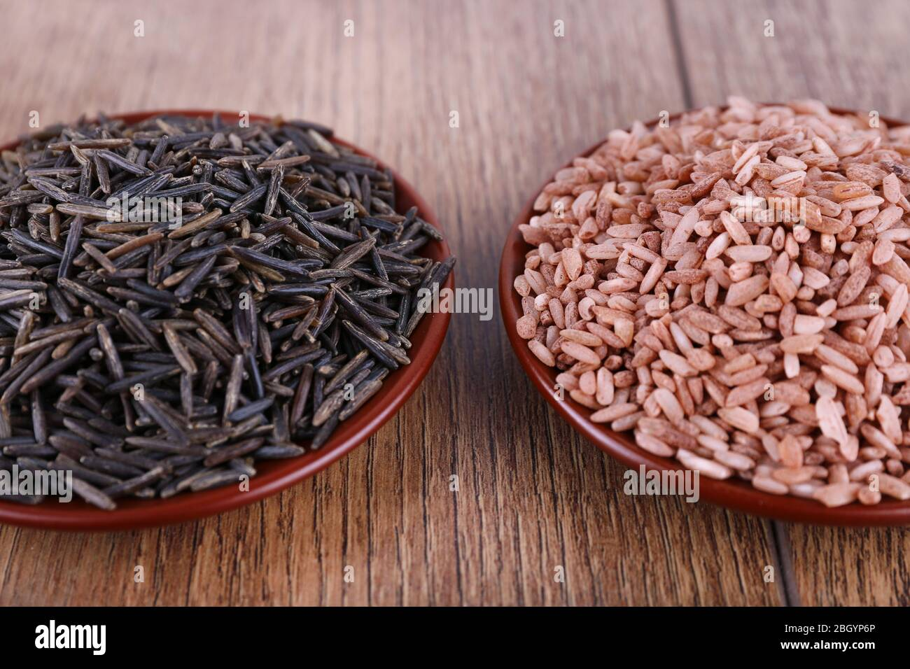 Red and black rice in pales on wooden background Stock Photo
