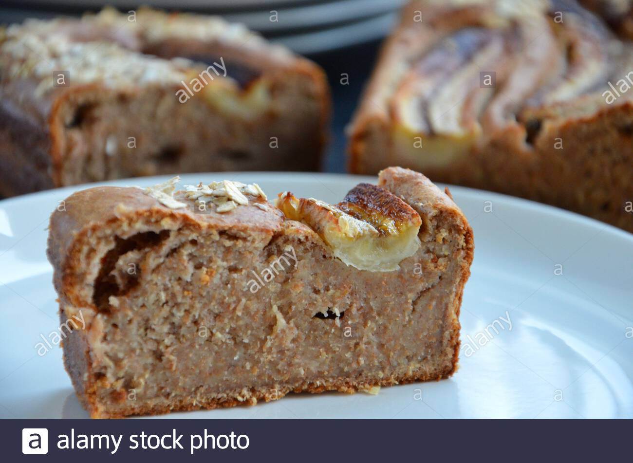 Homemade banana walnut bread made from wholemeal flour, oat flakes on top, one slice on a white porcelain plate, blurred background Stock Photo