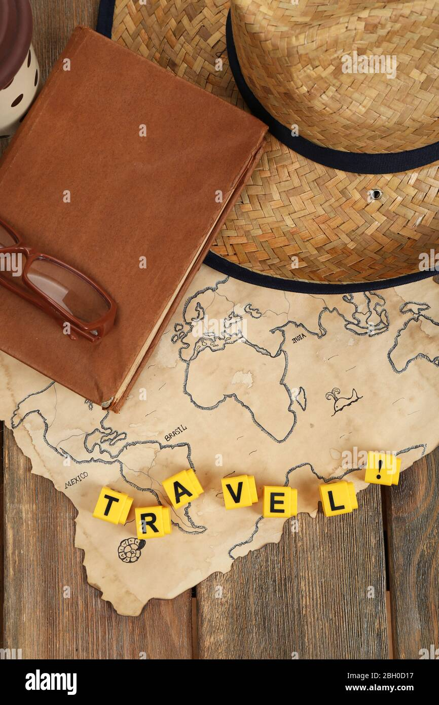 Straw hat, book and glasses with word Travel on world map and wooden planks background Stock Photo