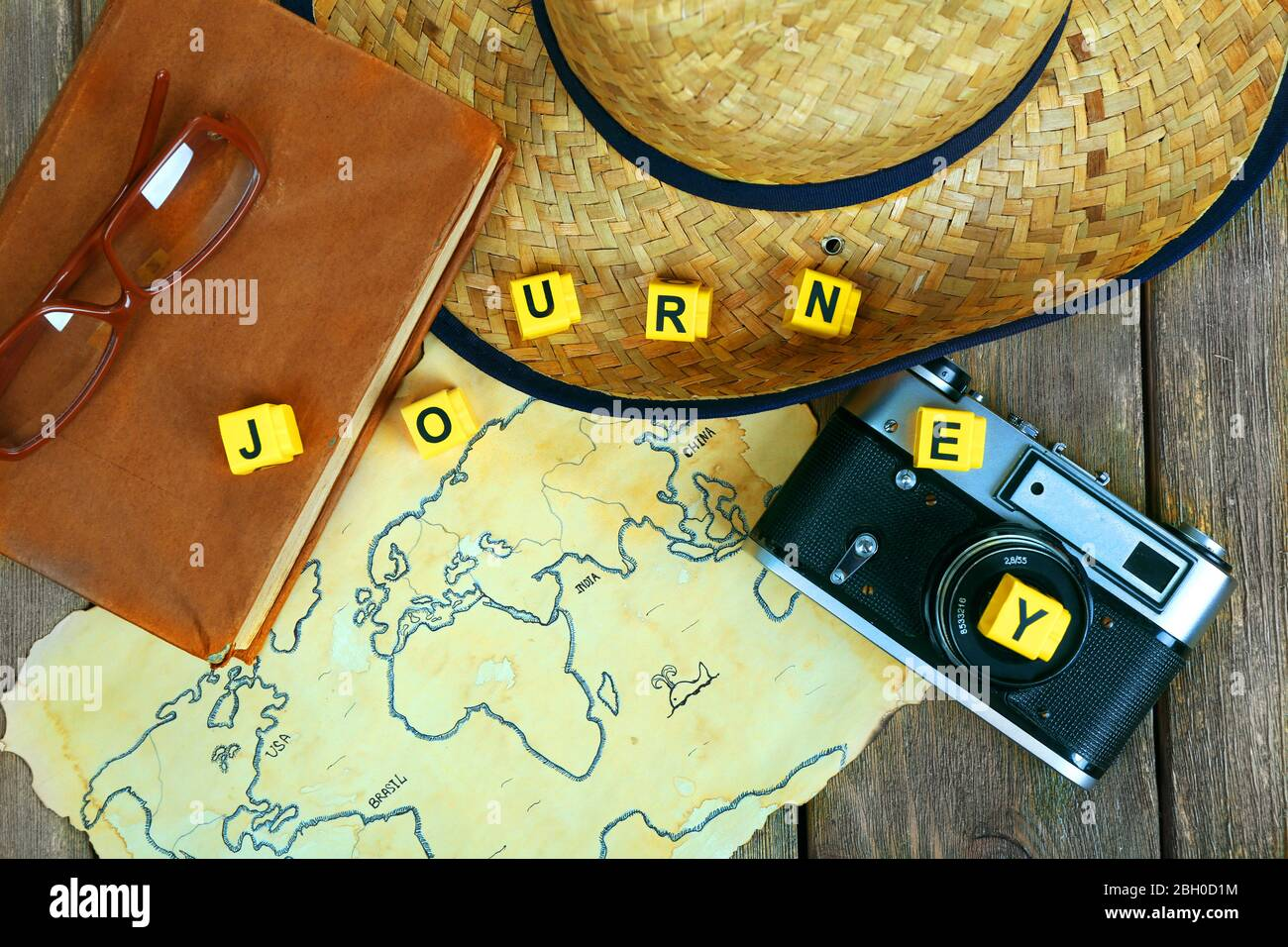 Straw hat, book, camera and glasses with word Journey on world map and wooden planks background Stock Photo