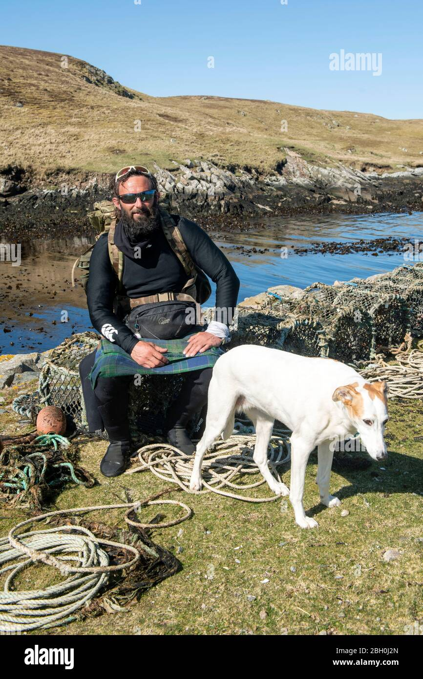Hildasay, Shetland, Scotland, UK , 22nd April 2020, Ex-Paratrooper and charity walker Chris Lewis and his companion Jet on the island of Hildasay on the west coast of Shetland were they are self isolating during the COVID-19 pandemic. Chris is on a charity walk around the coast of the UK which he started in 2017. All money raised goes towards the SSAFA armed forces charity. The island of Hildasay is an uninhabied island and Chris and Jet are the only occupants during this tme. Photo:Dave Donaldson Credit: Dave Donaldson/Alamy Live News Stock Photo