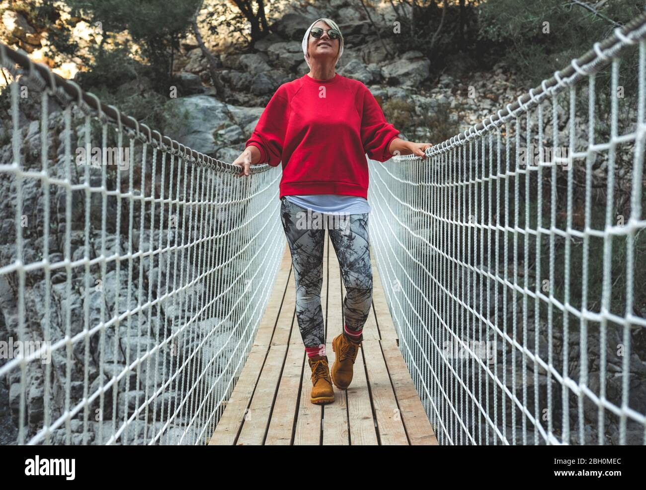 Adult woman standing on a hanging wooden bridge in the nature. Female hiker in Goynuk Kanyonu in Antalya,Turkey. Stock Photo