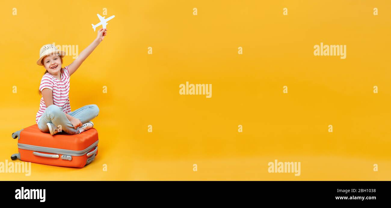 Happy little girl sitting on a suitcase and holding a paper airplane on a yellow background. The child dreams of travel and relaxation. Copy space. Stock Photo