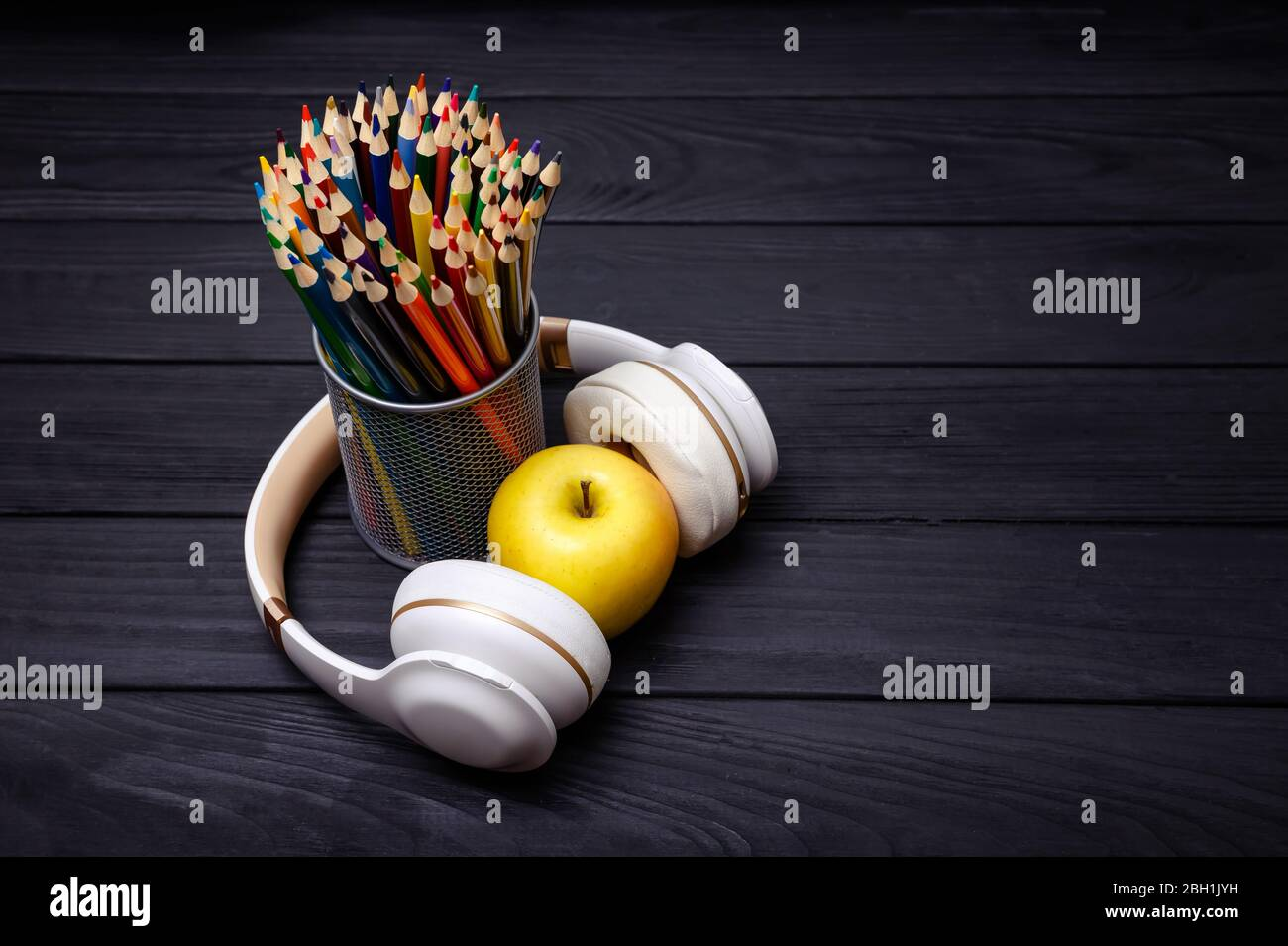 Colorful pencils and headphones on black wooden background. Workplace Stock Photo