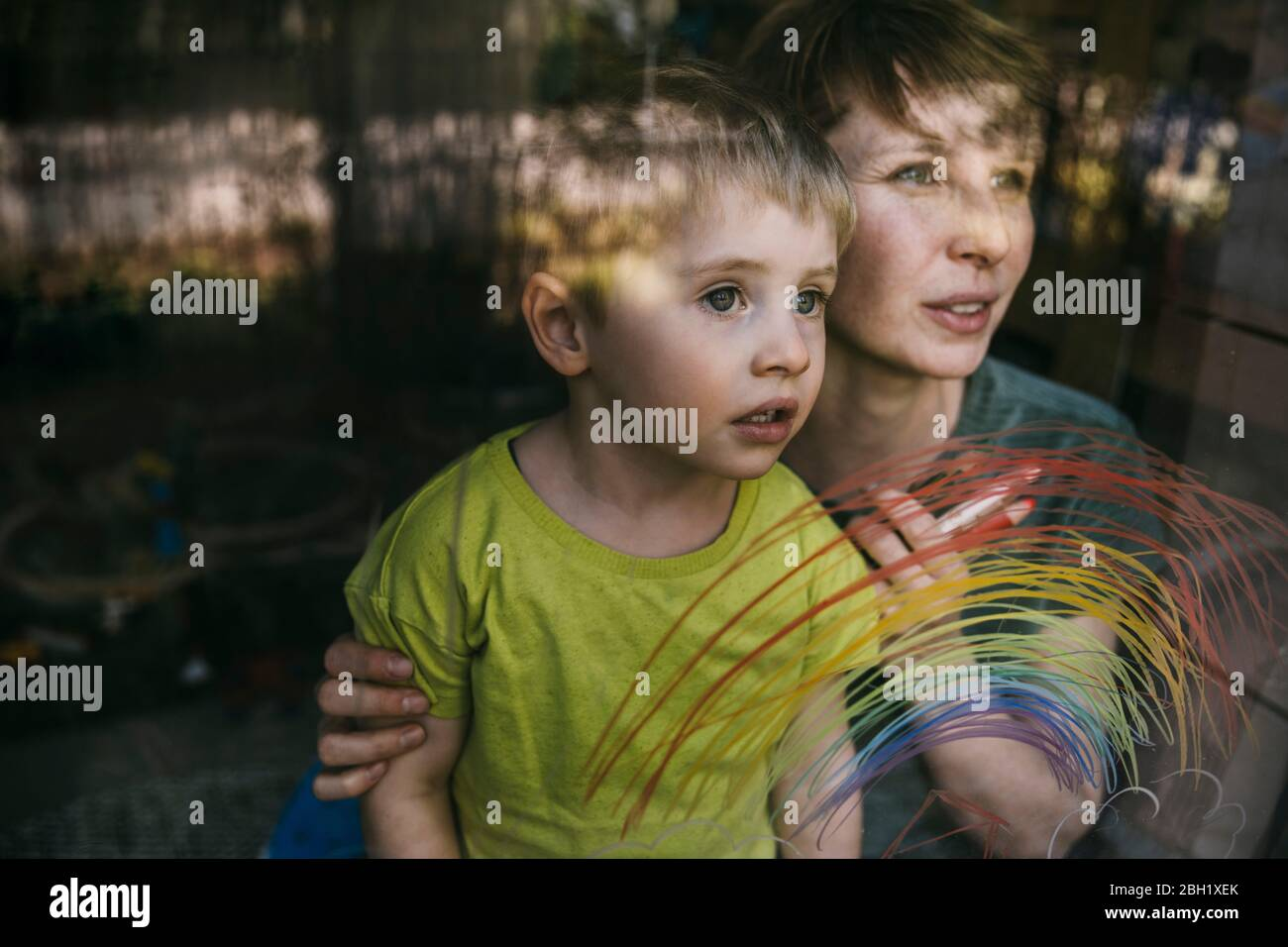 Portrait of mother and her little son looking out of window with drawn rainbow Stock Photo