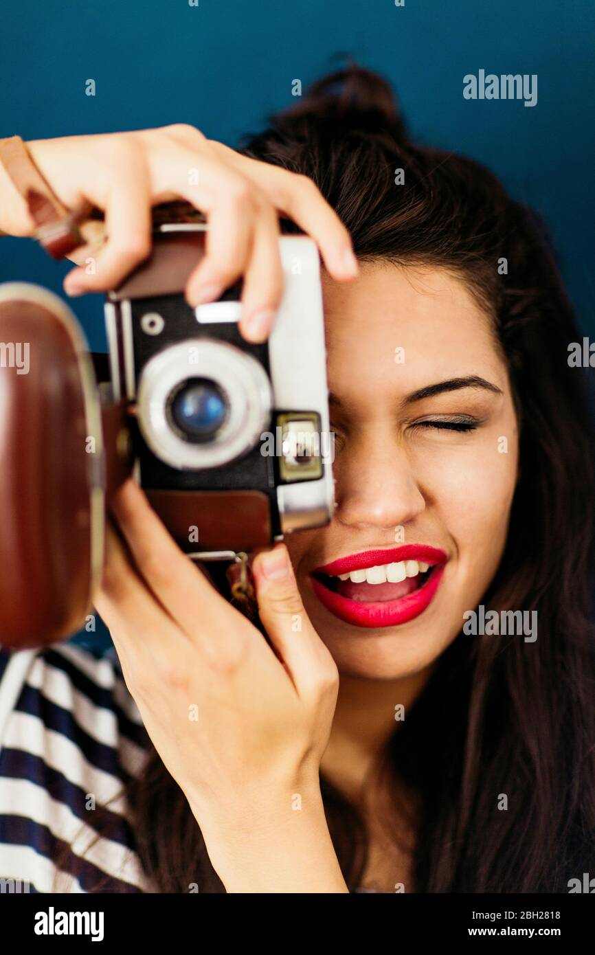 Portrait of young woman with red lips taking picture of viewer with camera Stock Photo