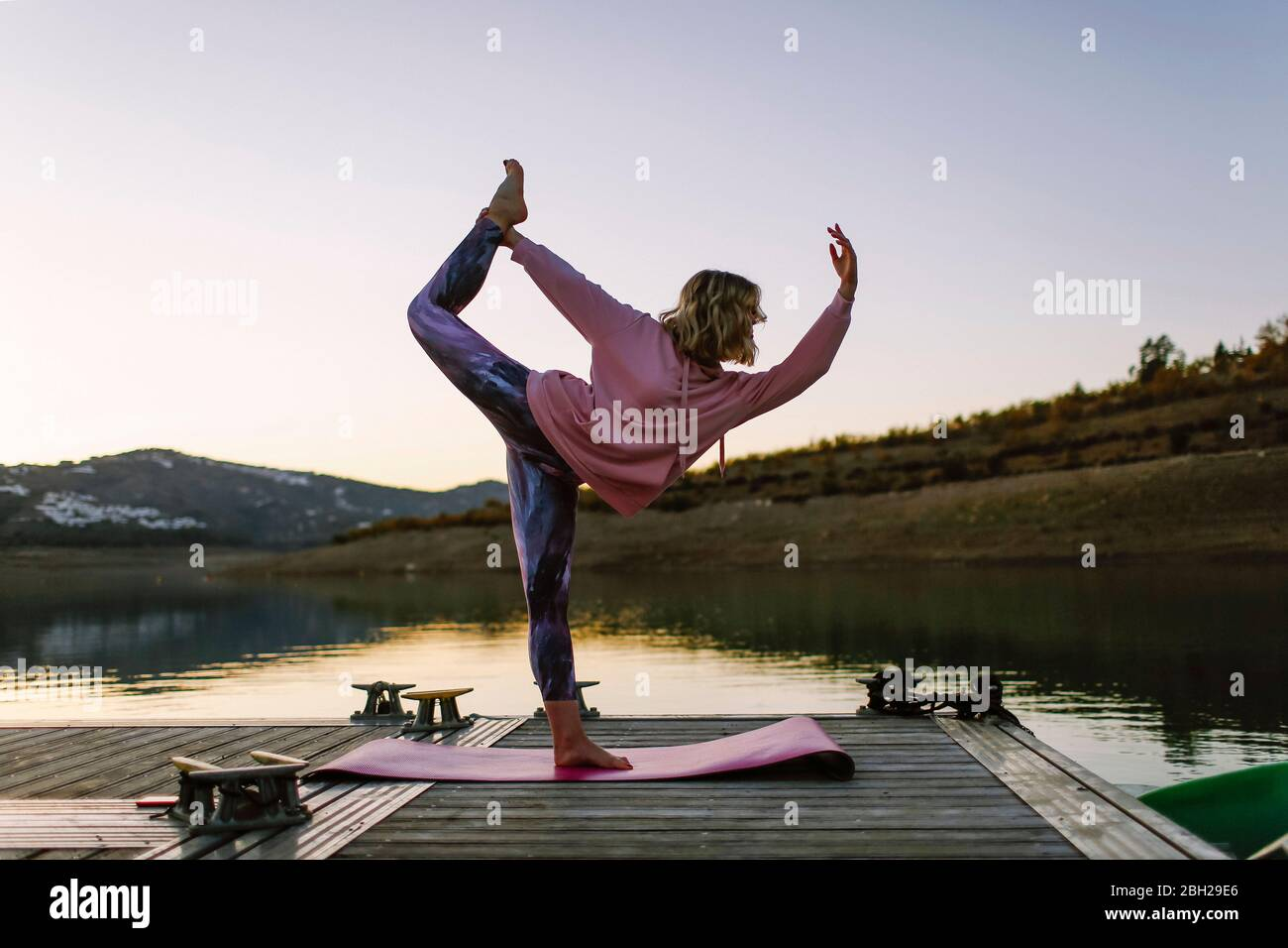 Young woman doing yoga on a jetty, dancer position Stock Photo