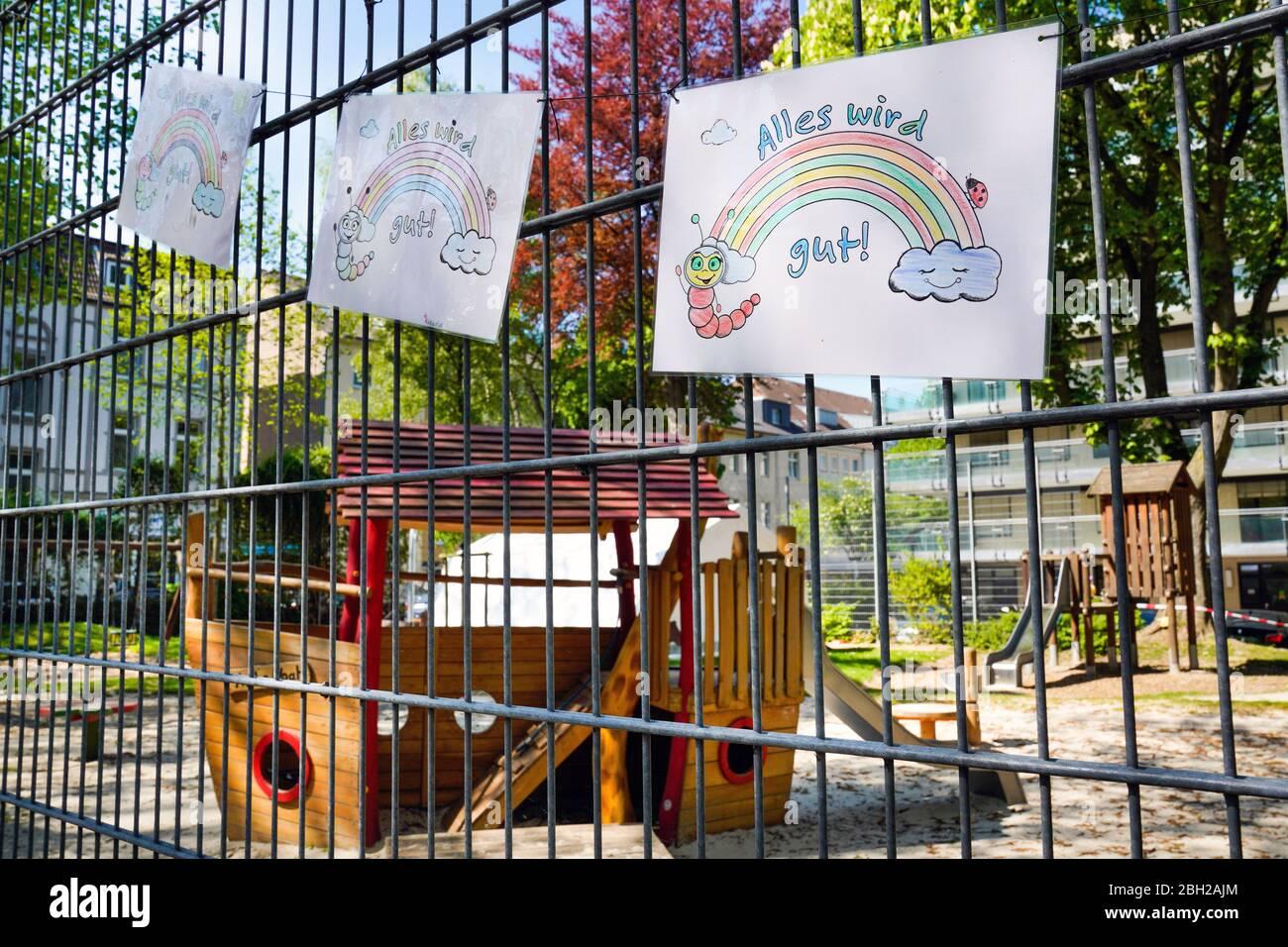 """Dortmund, 23.04.2020: Von Kindern gemaltes Plakat mit der Aufschrift """"Alles wird gut"""" hängt am Zaun eines Kinderspielplatzes, der wegen der Gefahr vor Ansteckung mit dem Corona-Virus Covid-19 gesperrt ist.   ---   Dortmund, Germany, April 23, 2020: Poster painted by children with the inscription """"Everything will be fine"""" hangs on the fence of a children's playground, which is blocked due to the risk of infection with the Corona Virus Covid-19, SARD-CoV-2 Stock Photo"""