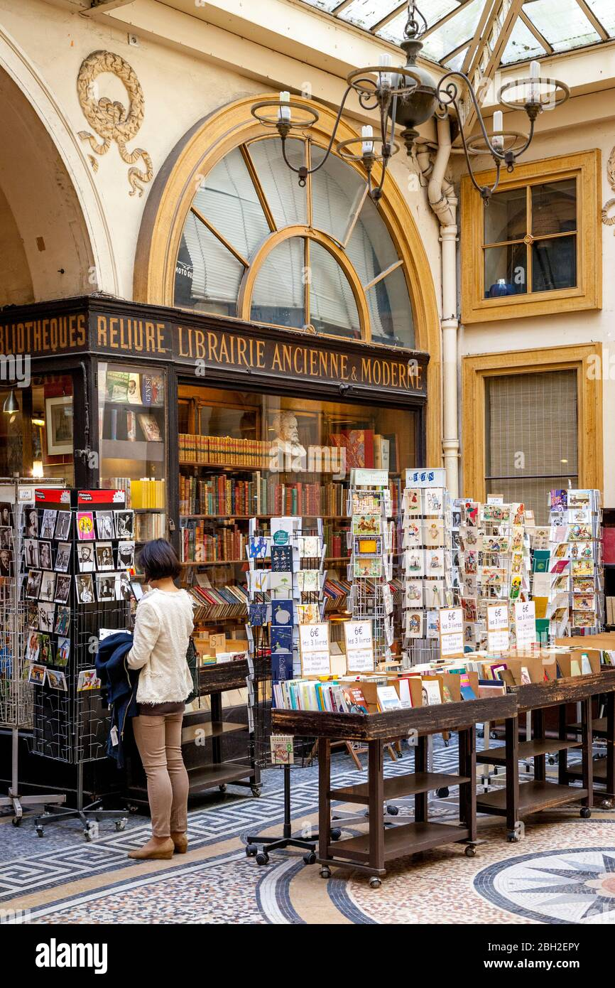Young woman shopping at an antique bookstore in Passage Vivienne, Paris, France Stock Photo