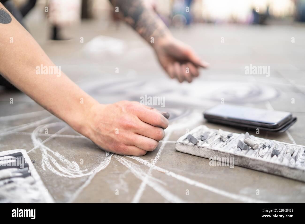 Street art, pavement artist drawing on pavement and using smartphone Stock Photo