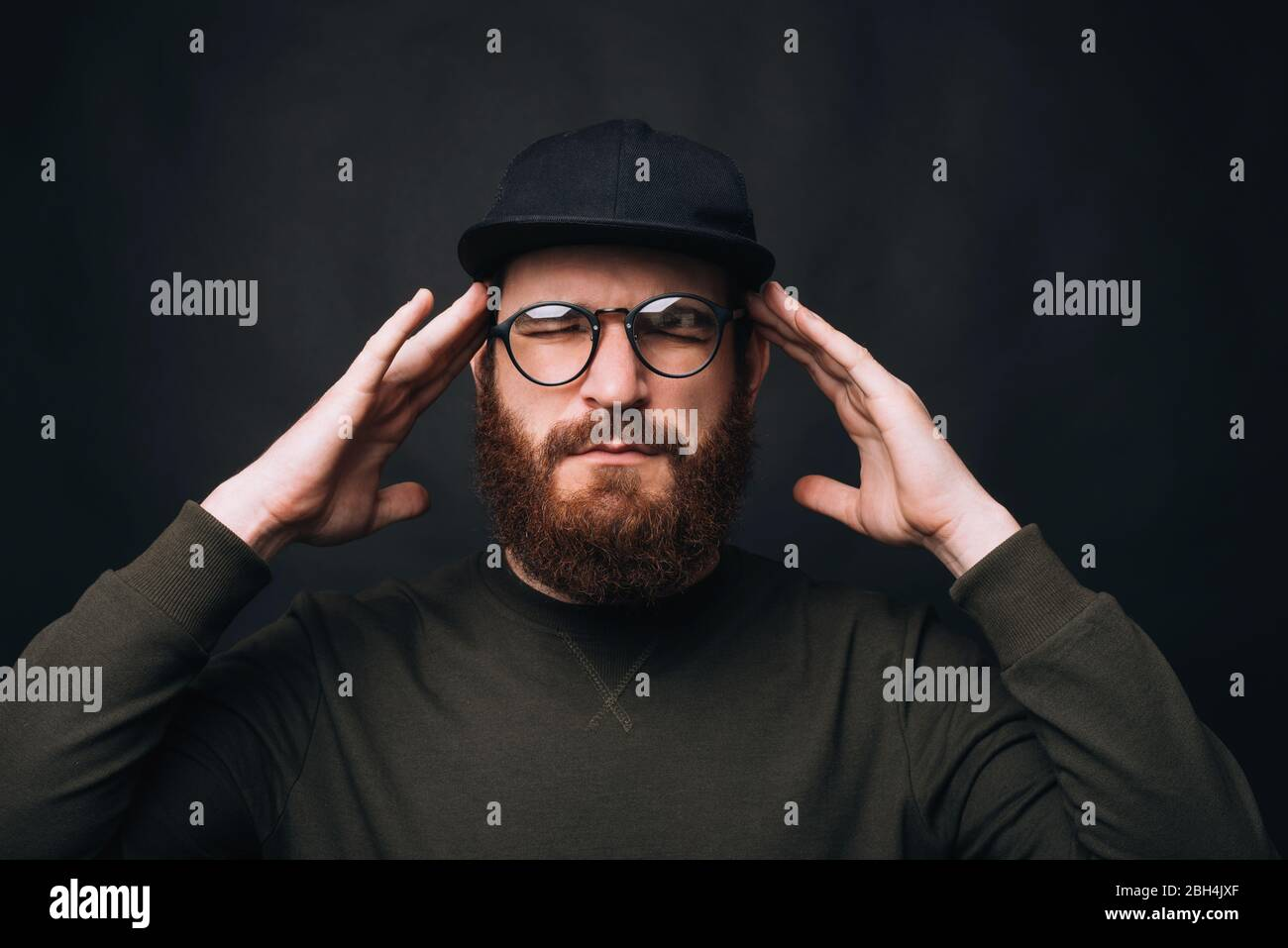 Concentrate. My head hurts. I am having a headache. Bearded man with eyes closed touching head on black background. Stock Photo