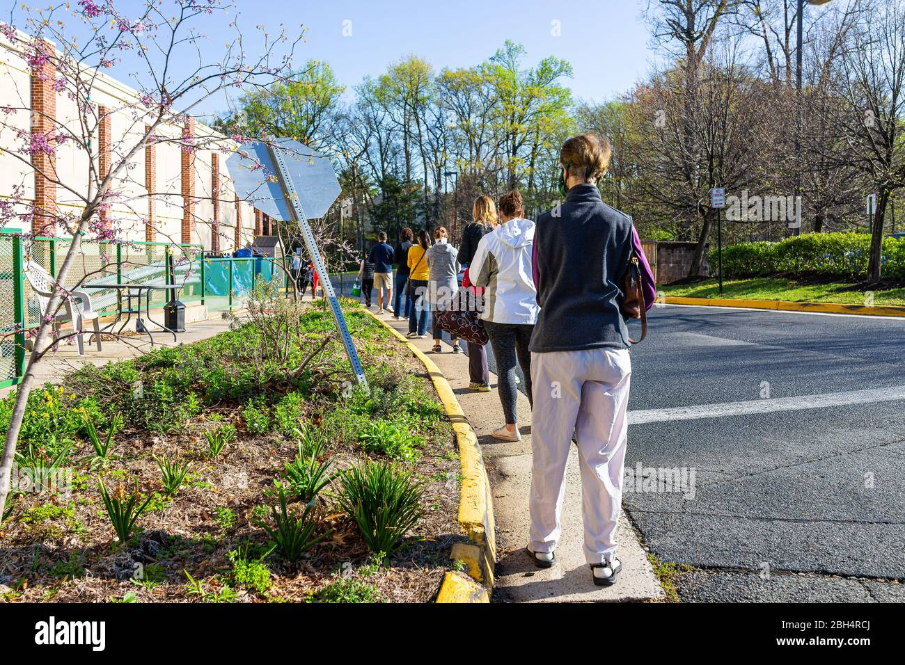 Reston, USA - April 9, 2020: Social distancing of people waiting in line queue by Trader Joe's grocery shop due to limit for customers in store during Stock Photo