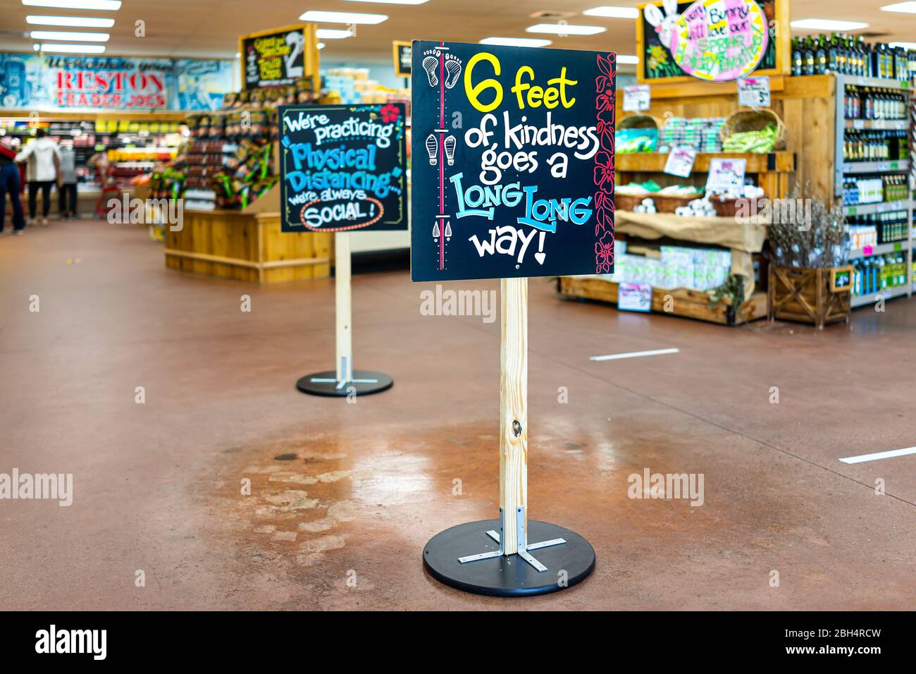 Reston, USA - April 9, 2020: Social distancing sign inside Trader Joe's grocery shop store during coronavirus with empty interior Stock Photo