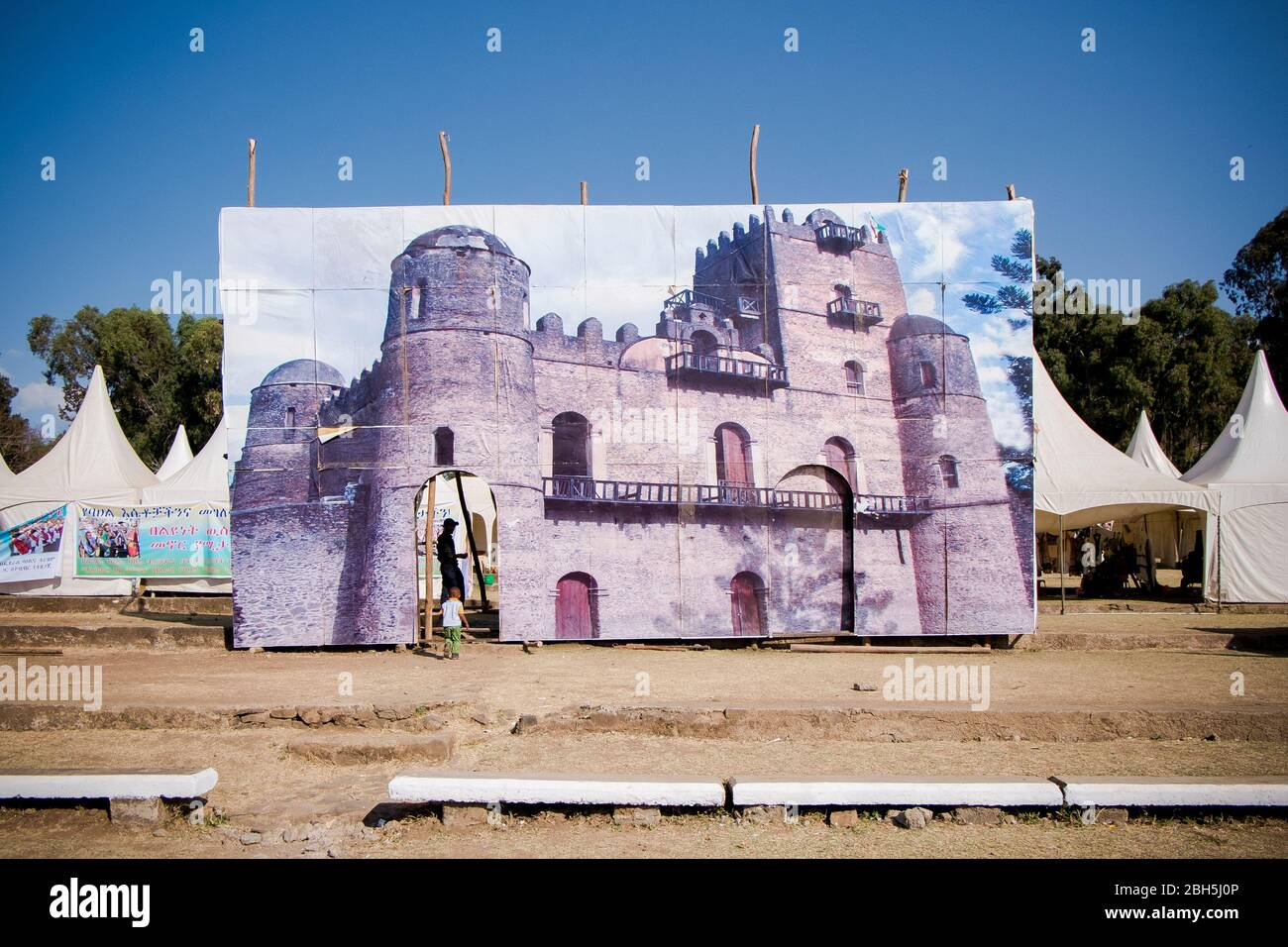 A little boy walks through a giant image of Fasilides castle at a Timkat festival ground. In Gondar, Ethiopia, Africa. Stock Photo