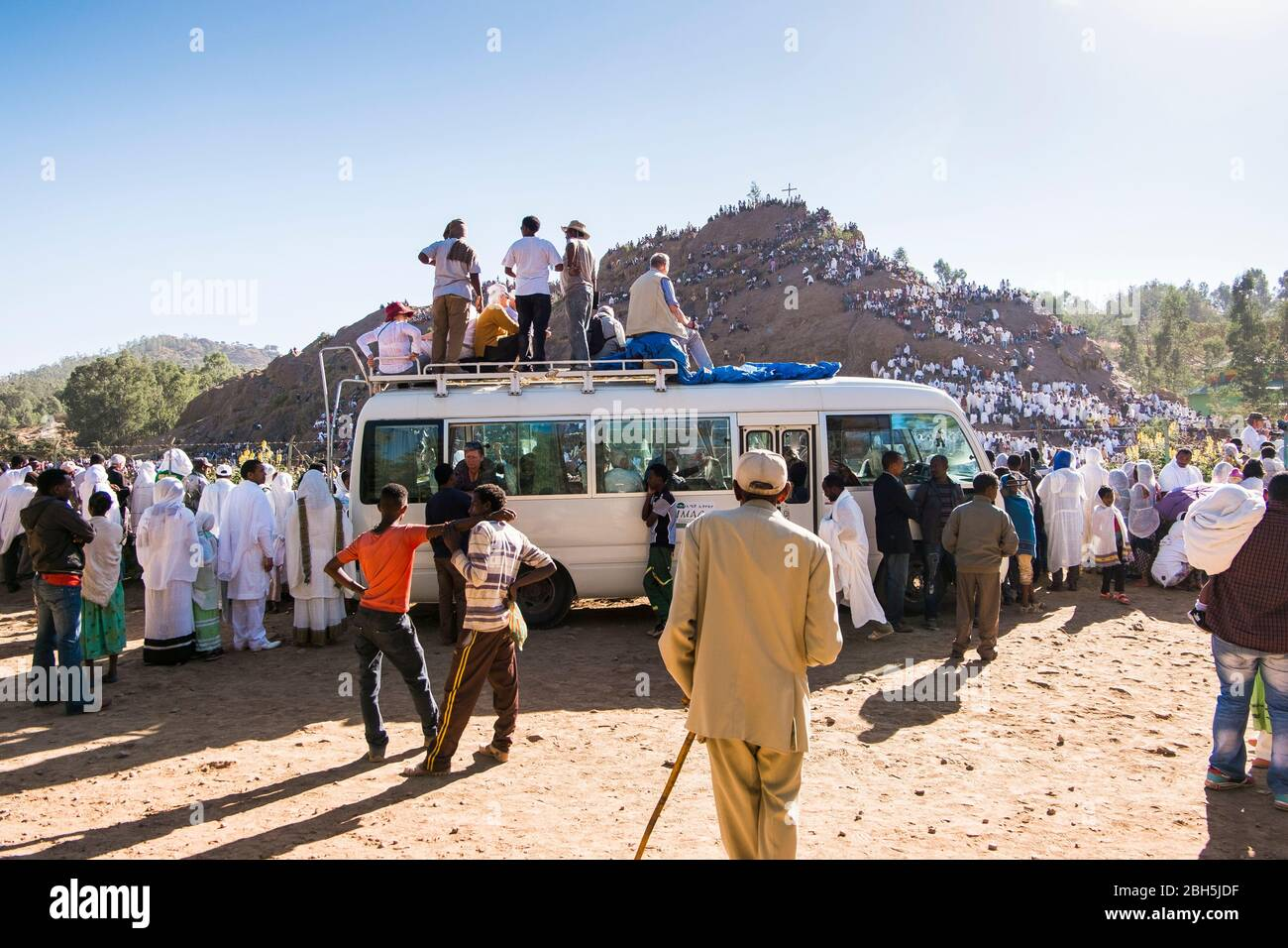 Western tourists sit on their van in order to better witness the Timkat ceremony in Axum. In Ethiopia, Africa. Stock Photo