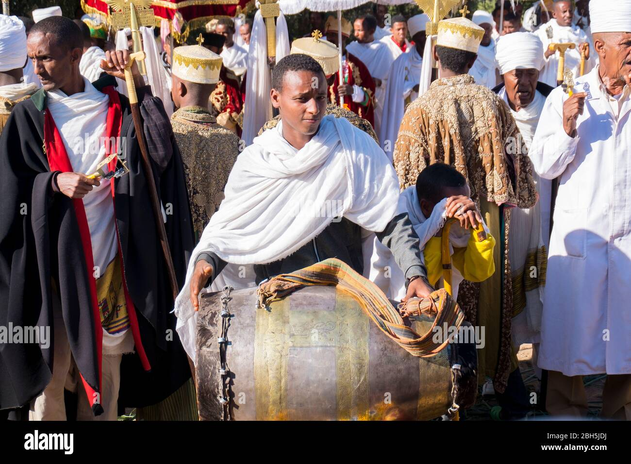 A young man is busy drumming dring a Timkat ceremony in Axum. In Ethiopia, Africa. Stock Photo