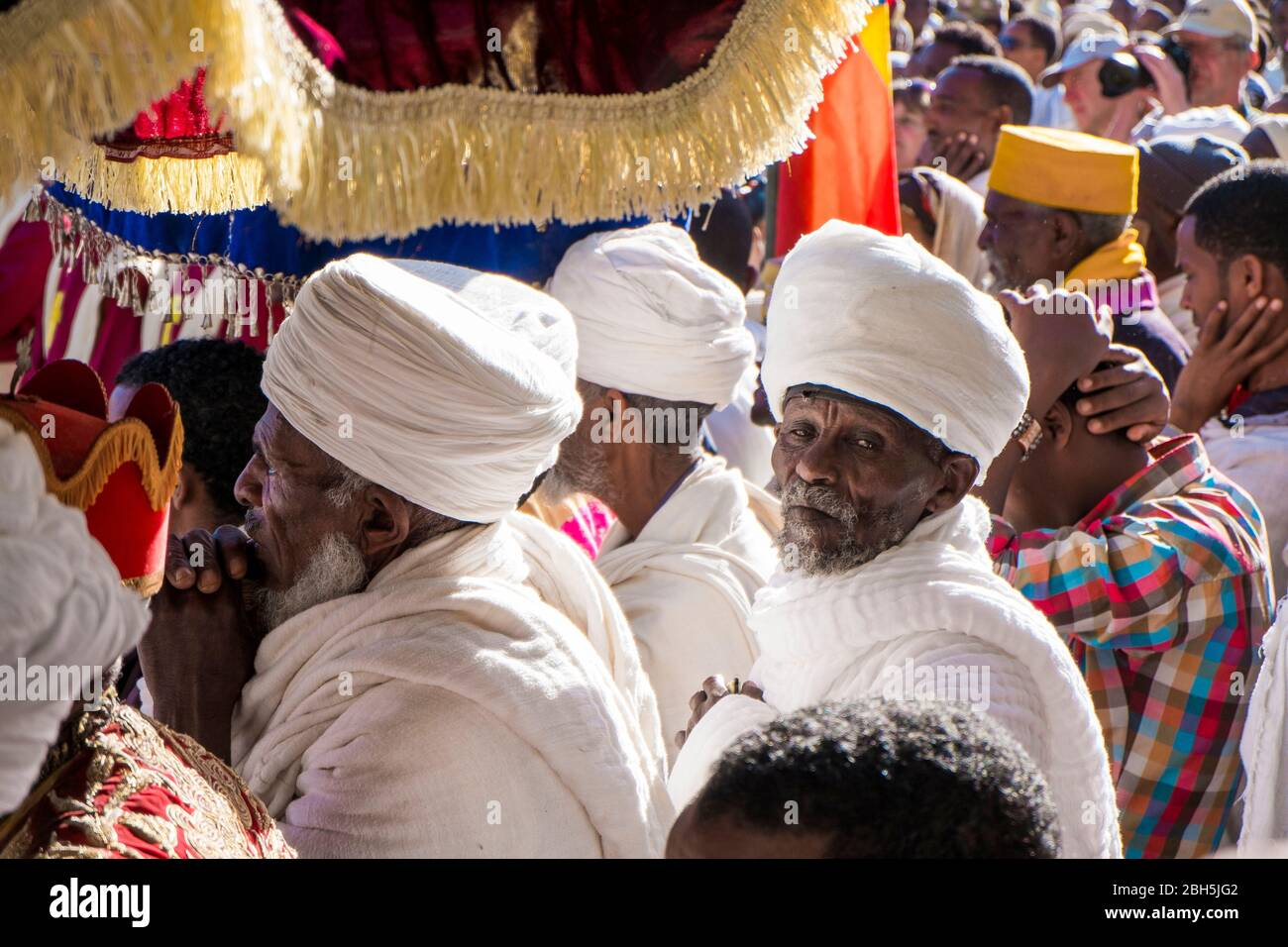 Old men, with wrapped white head turbans, listen during a Timkat ceremony in Axum. In Ethiopia, Africa. Stock Photo