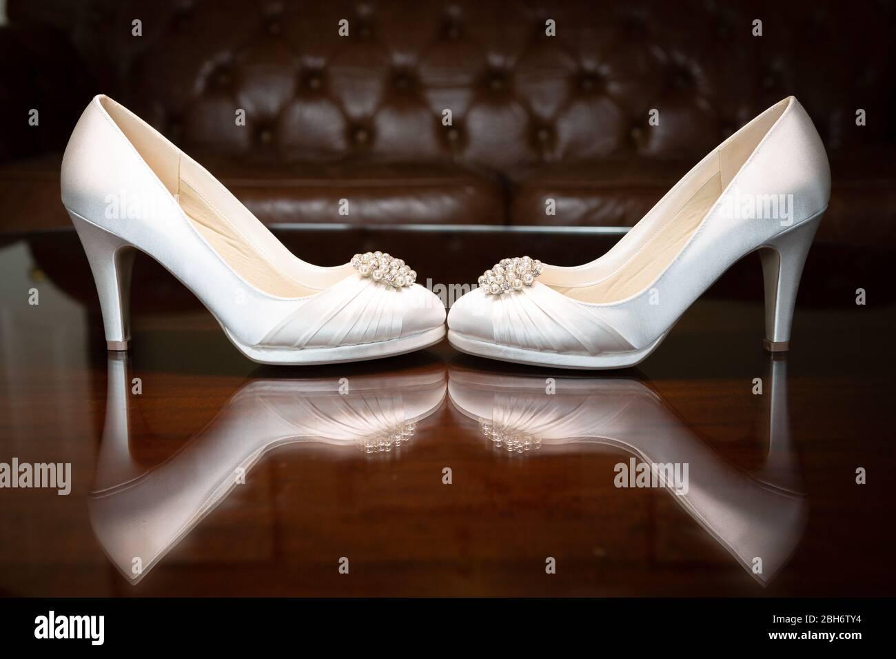 Luxury Wedding Shoes sitting on a reflective surface Stock Photo