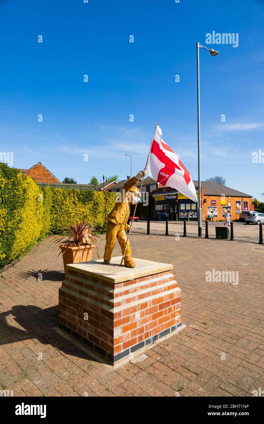 """Carved, wooden """"Clockpelters"""" statue wearing medical mask during the Covid-19 pandemic, on St Georges Day with an England flag. Great gonerby, Grantha Stock Photo"""