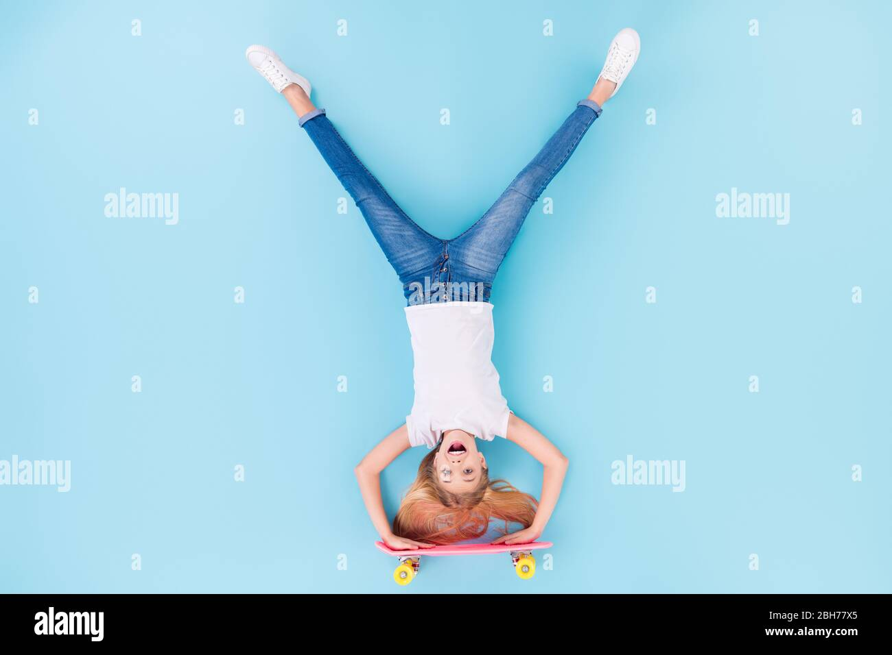 Top above high angle view full body photo of positive girl sporty kid ride longboard upside down show tongue out wear white clothes lay isolated over Stock Photo