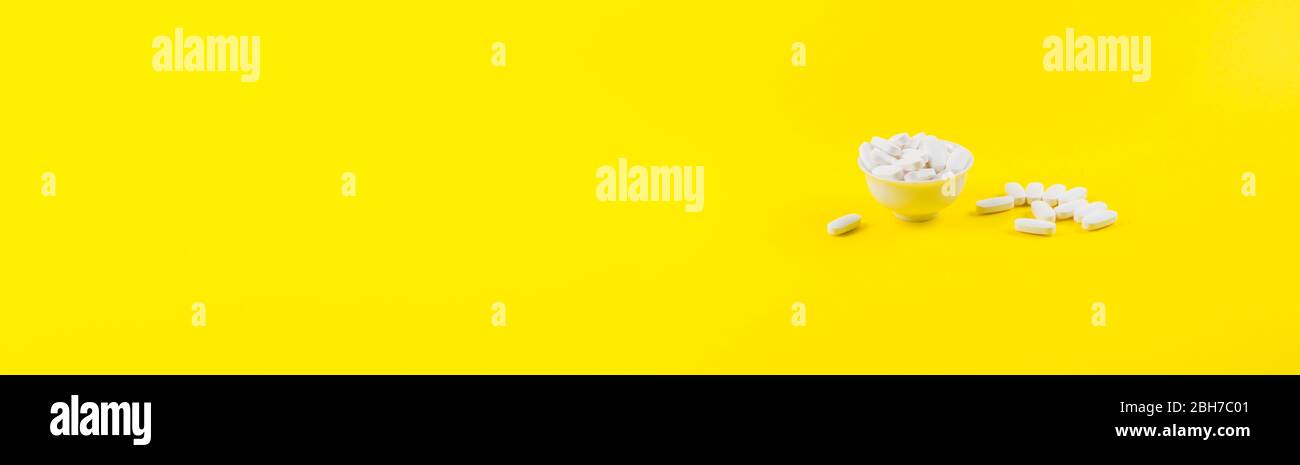 White magnesium citrate pills on yellow background Stock Photo