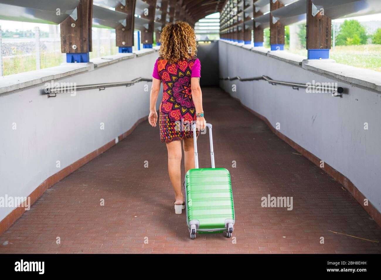 beautiful young curly blonde woman viewed from back rear travel and move walking with a green cabin bag luggage trolley. black dark tunnel in front of her in the background Stock Photo