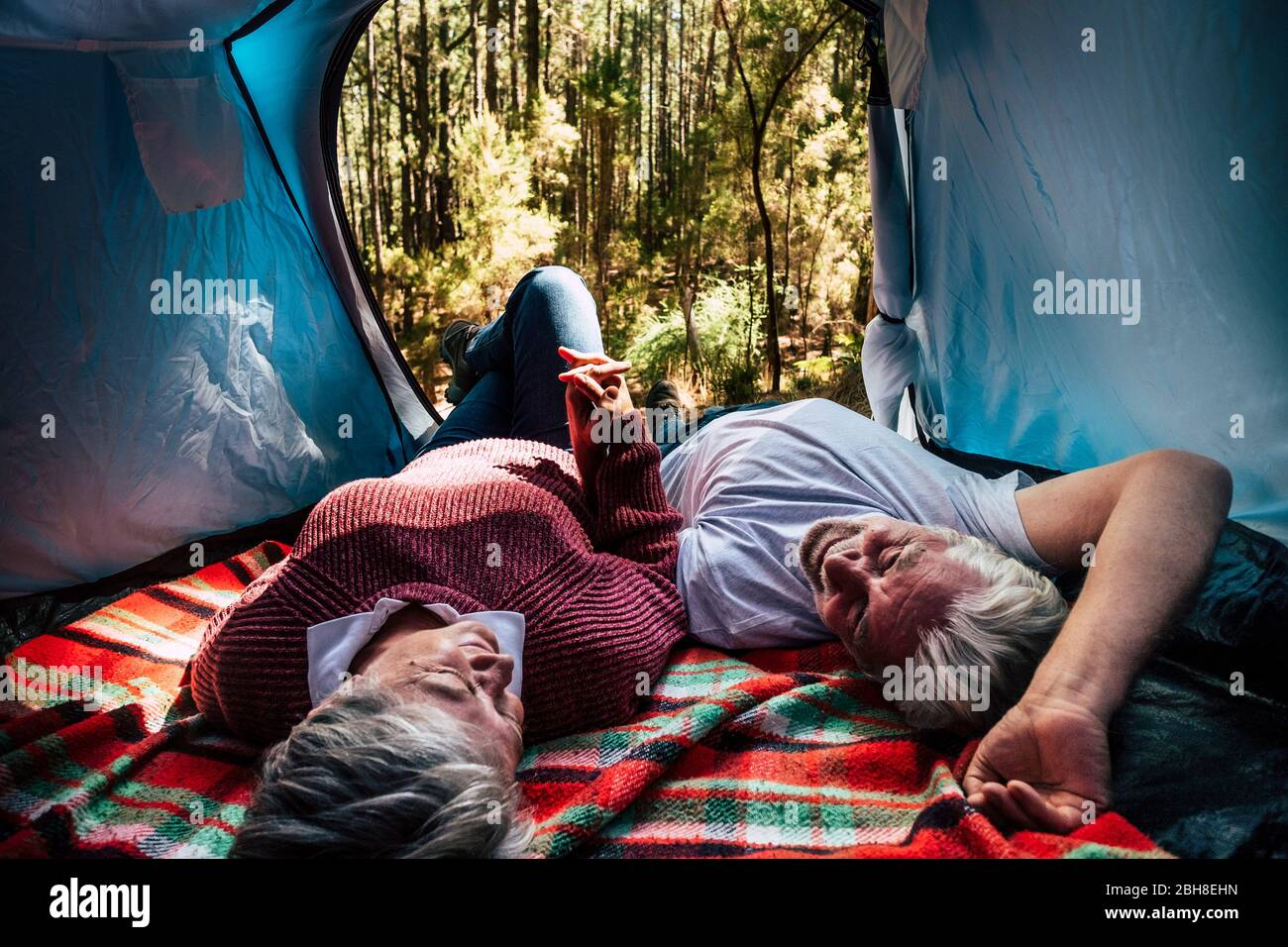 adult senior couple rest lay down inside a tent in free wild camping in the forest for alternative travel and lifestyle. Love forever together concept for man and woman taking hands andd look eachother - outdoor nature activity Stock Photo