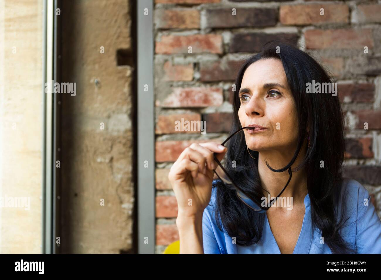 Close-up of thoughtful mature woman with eyeglasses looking through window at cafe Stock Photo