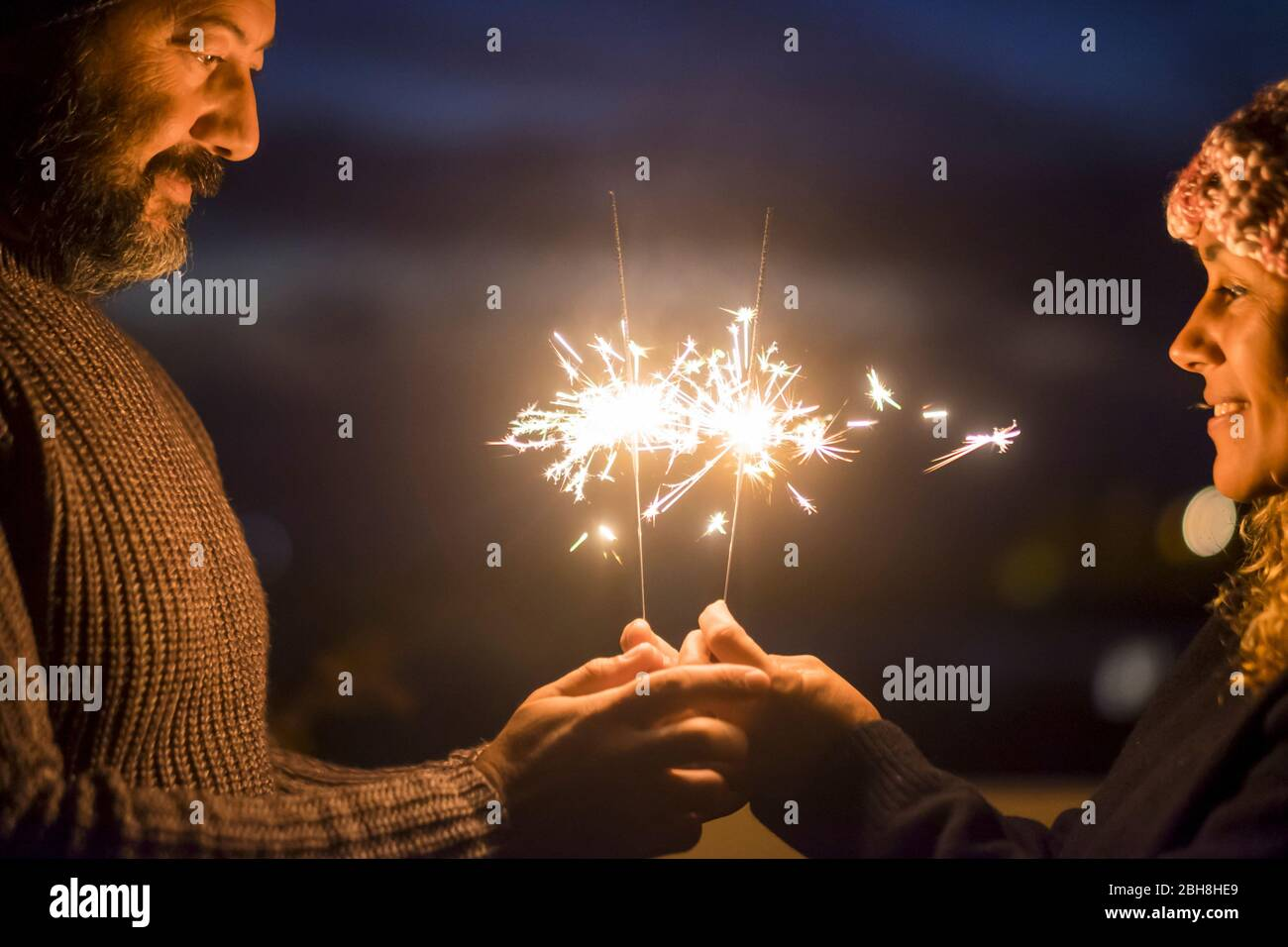 Valentine's day and love concept celebration for caucasian middle age beautiful couple enjoying together lifestyle and and togetherness life with sparklers light in the night - happy people Stock Photo