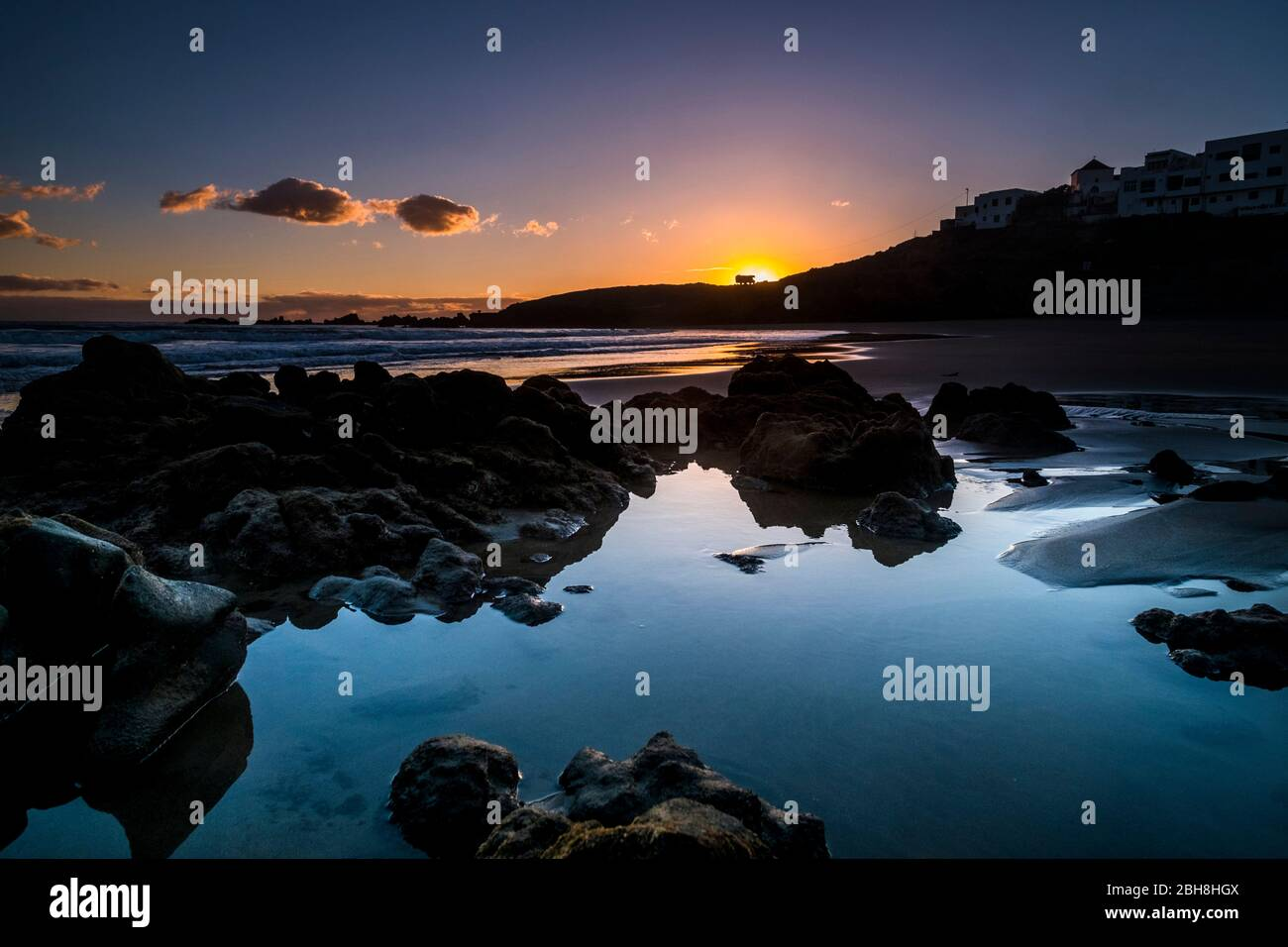 Sunrise or sunset at the ocean beach - beautiful colors and wave and sky - environment and vacation scenery place concept - landscape with coastal city and red clouds - magic light before the day Stock Photo