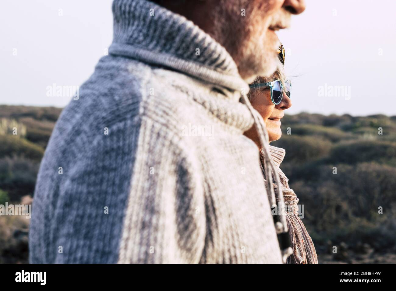 Portrait fashion style mature couple old aged seniors man and woman with nature in background - cold season autumn or spring and sun Stock Photo
