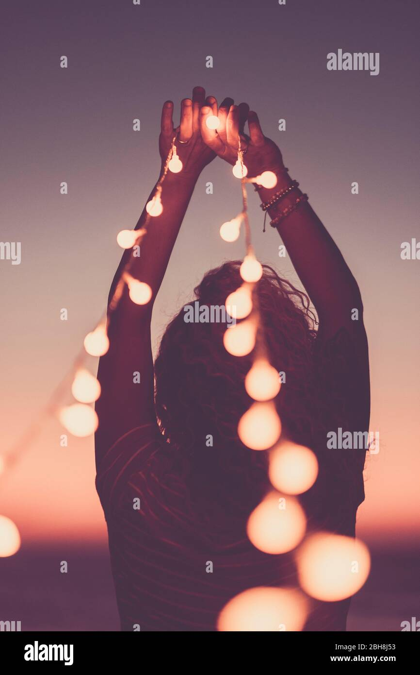 Motivational inspirational concept image with girl from back holding yellow bulb lights to the sky - pink coloured style filter - hope and feeling - lifestyle for happy people - sunset in background Stock Photo