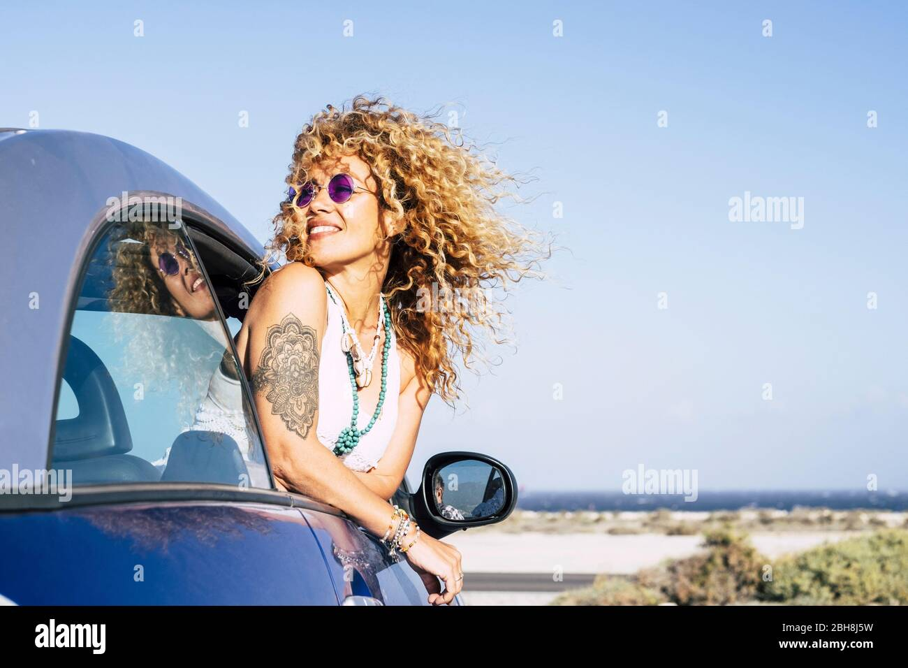 Beautiful cheerful happy caucasian woman outside the car with wind in curly long blonde hair - attractive people enjoying the freedom in outdoor coastline ocean vacation place Stock Photo