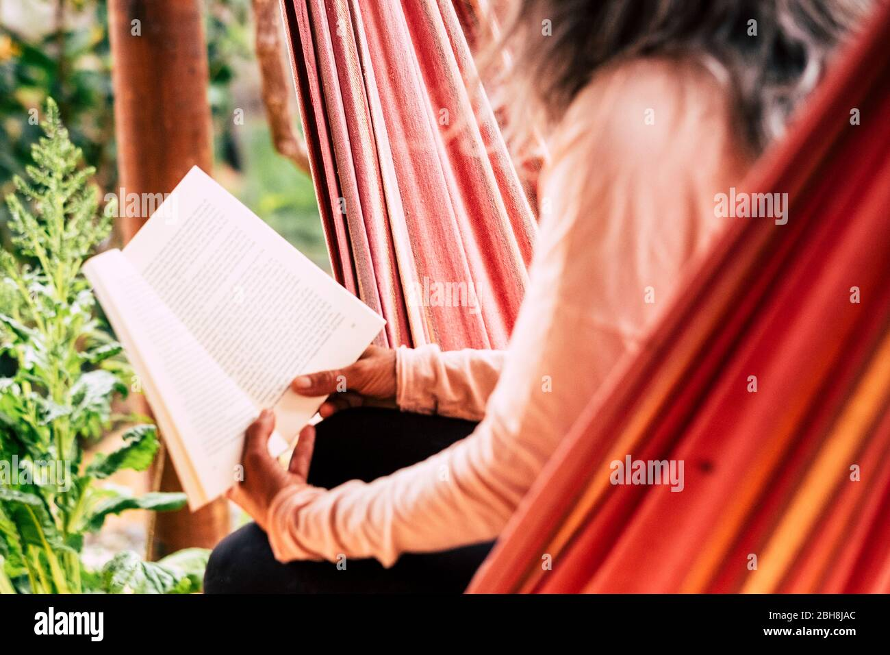 Reading a paper book old style concept to relax and study - aged caucsian woman with white hair sitting on an hammock outdoor enjoy the leisure activity Stock Photo