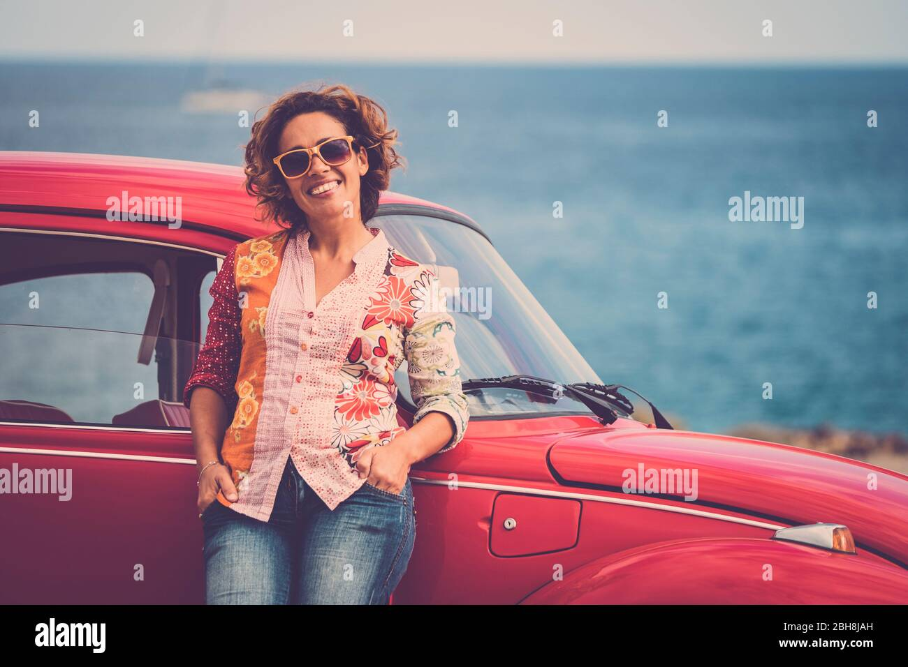 Beautiful caucasian middle age lady driver pose standing with a red legendary retro vintage car behind - ocean in background for travel and alternative lifesyle concept Stock Photo