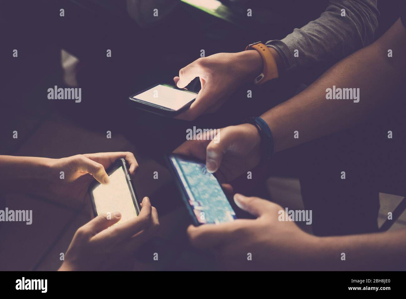 Three young caucasian teenager men play all together with mobile phone device to video games like clan or team - usual activity for millennial people at home - technology addicted people concept Stock Photo
