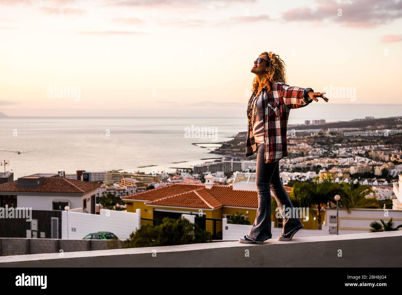 Creativity happiness freedom and craziness concept with young beautiful curly blonde woman walking in balance on a wall with city and coastline down in the background - cheerful people enjoy Stock Photo