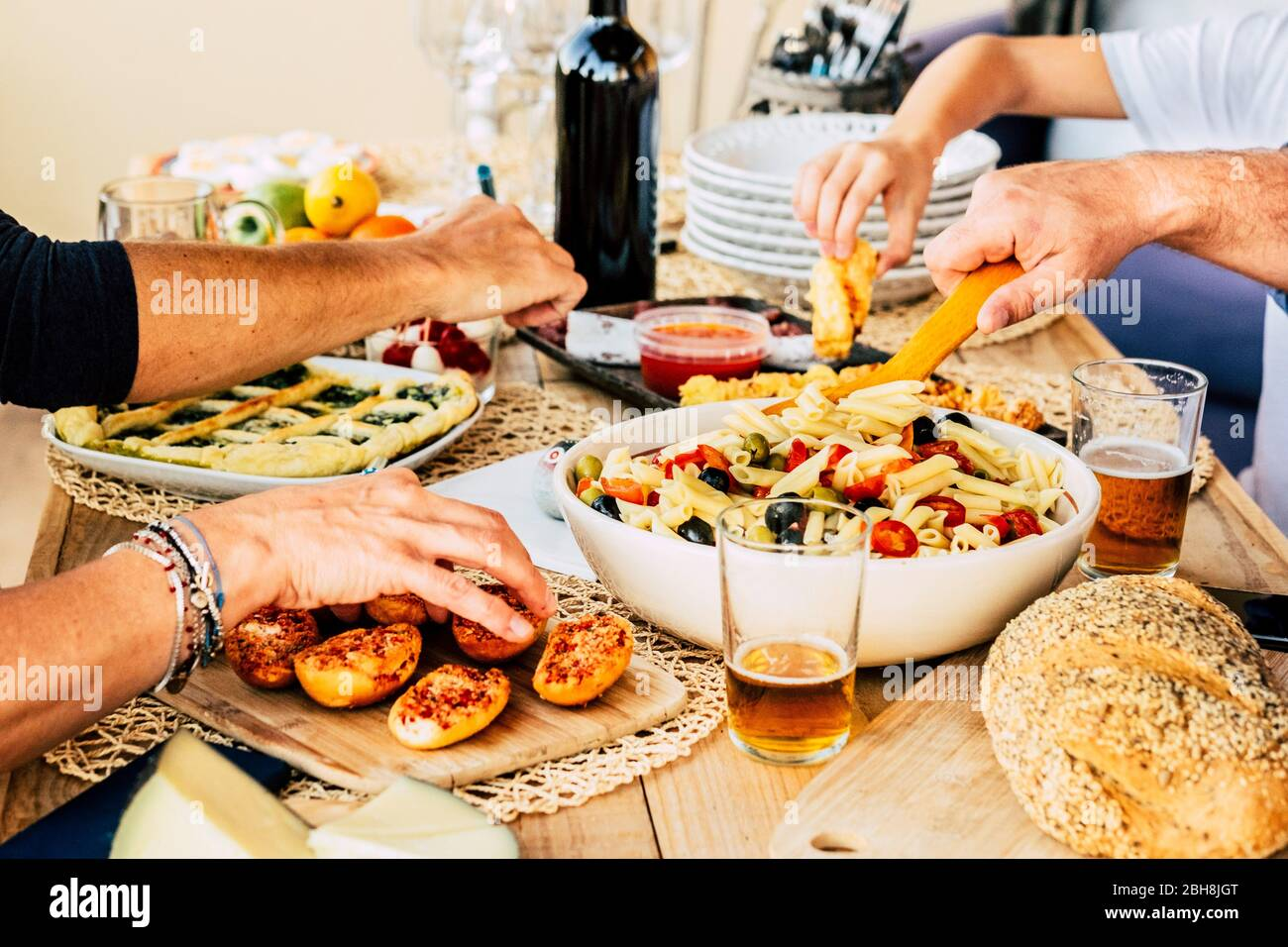 Group of caucasian friends enjoying together a happy lunch with italian meat lke pasta and pizza - beer and wine to have joy in friendship - wood table - home restaurant concept Stock Photo