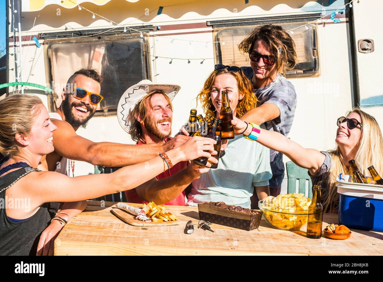 Group of happy friends tosting and clinking together beer with happiness - nice people with nature and outdoor lifestyle - boys and girls smiling and laughing with alternative caravan in background Stock Photo