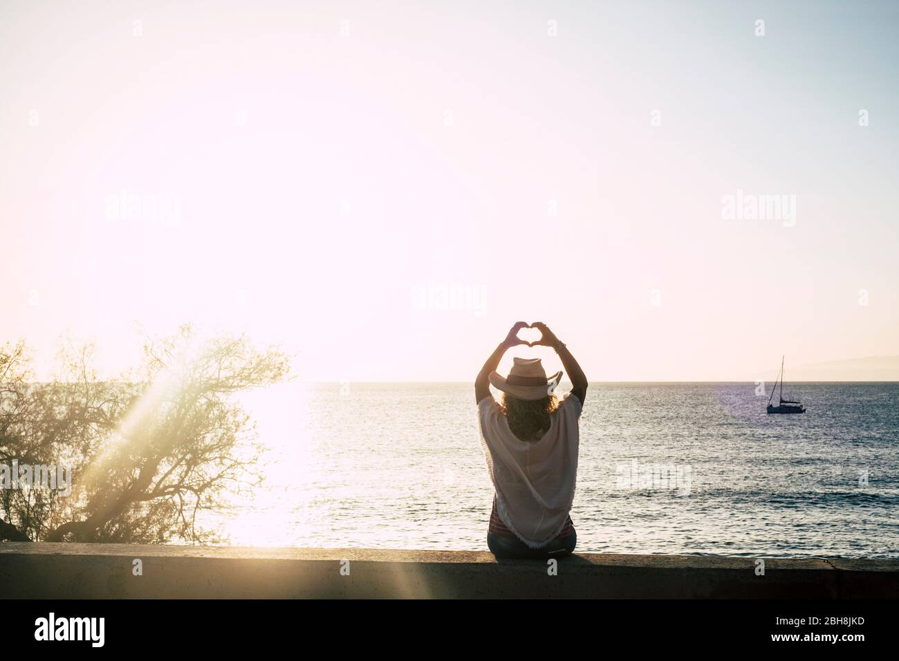 cute girl with cowbly summer style hat viewed from back doing hearth sign with hands - sun backlight and ocean with boat in background - freedom and enjoy lifestyle concept - clear sky Stock Photo