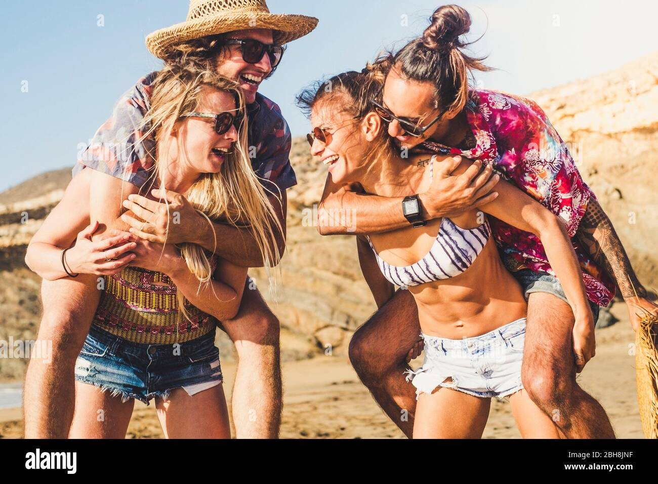 Cheerful happy group of people friends laugh a lot outdoor at the beach - summer travel vacation concept with women carrying men - sun and funny lifestyle for alternative millennial - beautiful resort place Stock Photo