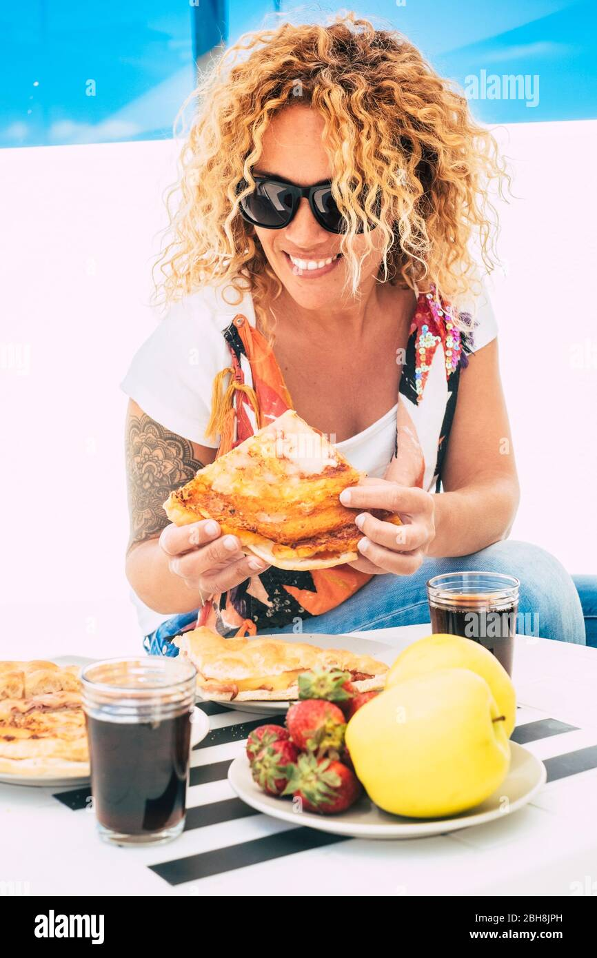 Beautiful cheerful curly long blonde hair woman eating italian pizza outdoor in restaurant or home terrace - trendy young female with tatoo and casual coloured style Stock Photo