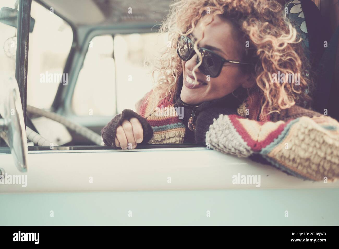 Cheerful happy beautiful caucasian young woman looking and smiling out of the window from old vintage van bus with sunglasses - travel driving concept for cute attractive girl with curly hair Stock Photo