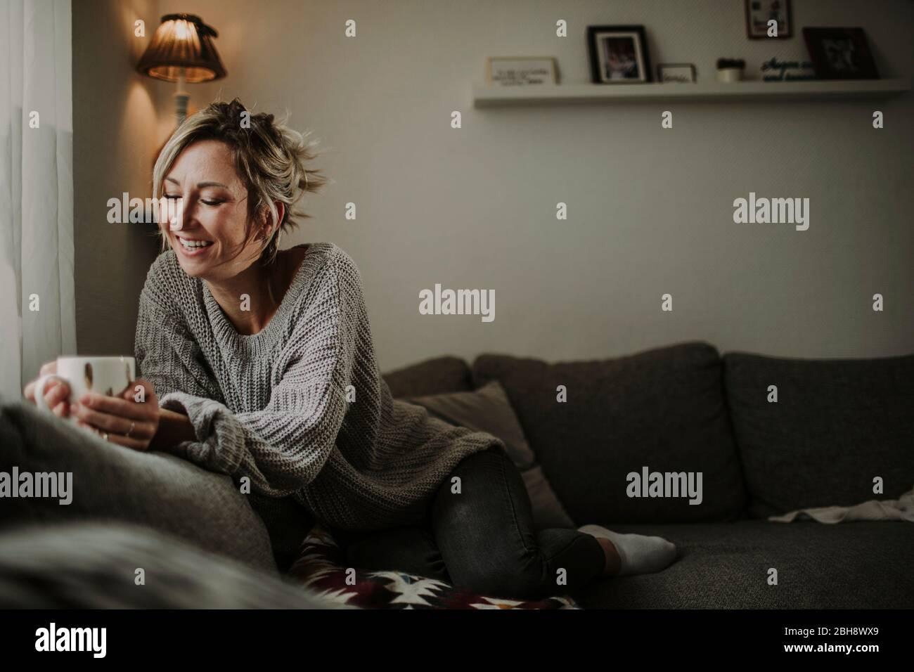 Frau mit Teetasse auf der Couch Stock Photo