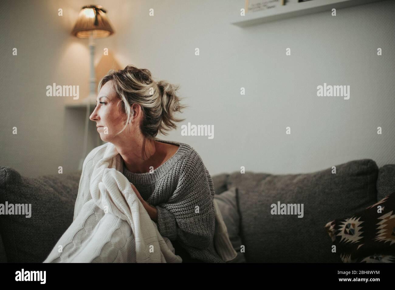 Frau sitzt nachdenklich auf der Couch Stock Photo