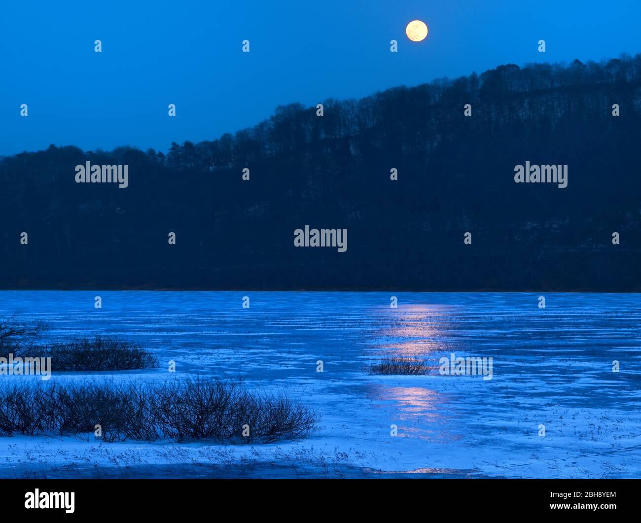 Europa, Deutschland, Hessen, Vöhl, Nationalpark Kellerwald-Edersee, Winterabend am vereisten Edersee, Vollmond, Spiegelung Stock Photo