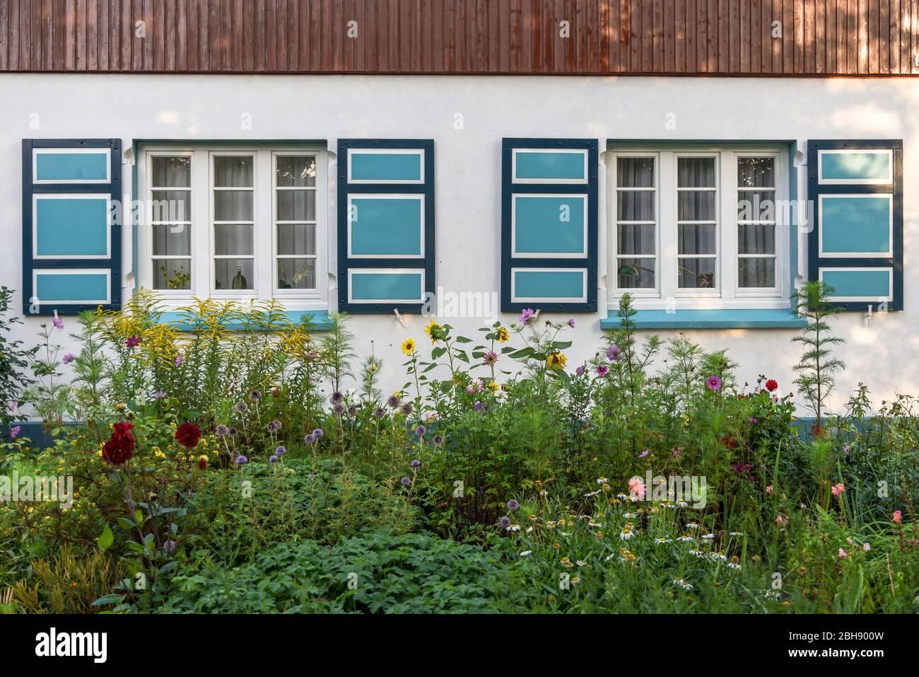 Hausfront mit bunten Fensterläden eines typischen Fischerhauses an der Ostsee auf dem Darß, Vorgarten mit bunten blühenden Sommerblumen Stock Photo